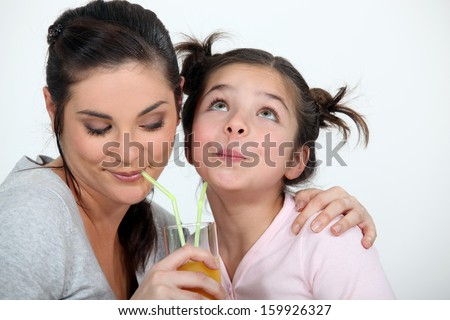 Mother and daughter sharing a drink - stock photo