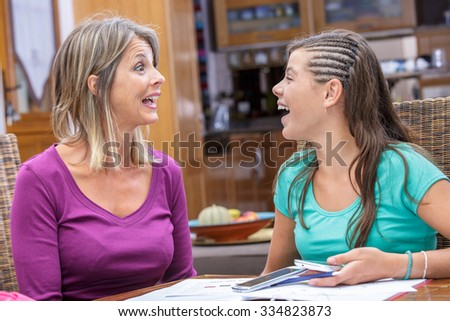 mother and daughter sharing a moment of complicity and laughing - stock photo
