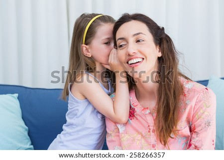 Mother and daughter sharing secrets at home in the living room - stock photo