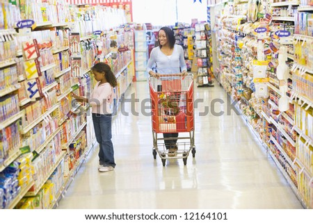 Mother and daughter shopping for groceries in supermarket - stock photo