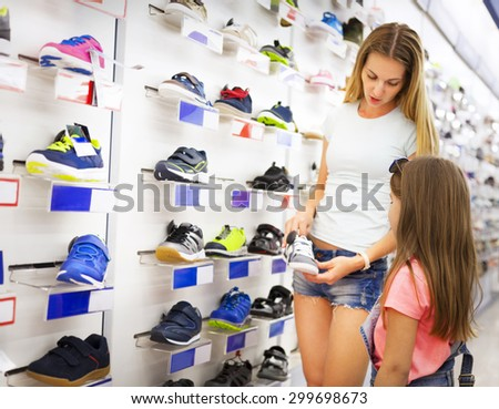 Mother and daughter shopping for shoes choicing sneakers - stock photo