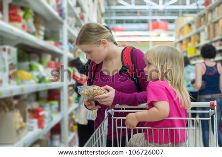 Mother and daughter shopping in cookies section in supermarket - stock photo