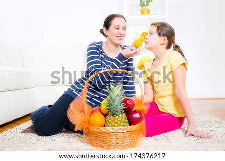 mother and daughter sit and pick fruit from the basket - stock photo