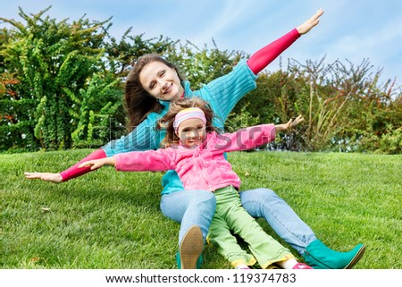 Mother and daughter sit on grass - stock photo