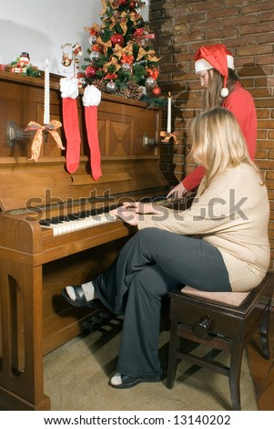 Mother and daughter sitting at the piano singing Christmas carols. Vertically framed shot. - stock photo