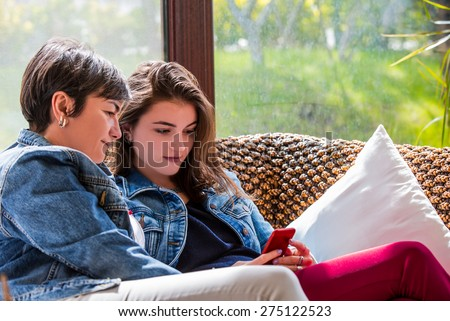 Mother and daughter sitting in a couch looking at the daughters smartphone. - stock photo