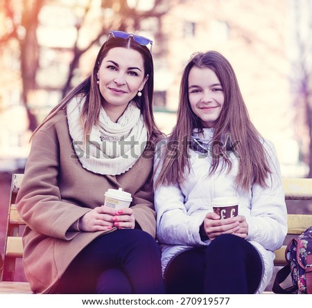 Mother and daughter sitting in autumn or spring park bench, are kept in the hands of cups of coffee or tea and smiling happy family. - stock photo