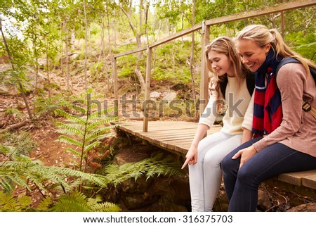 Mother and daughter sitting on bridge in a forest, side view - stock photo