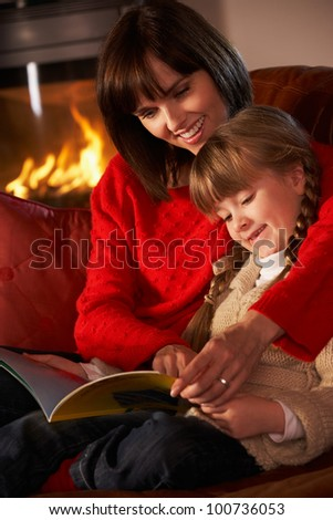 Mother And Daughter Sitting On Sofa And Reading Book By Cosy Log Fire - stock photo
