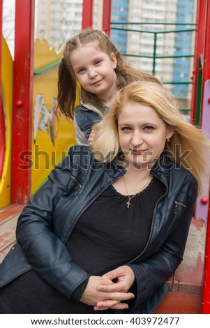 Mother and daughter sitting together on a playground. - stock photo