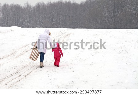 Mother and daughter sledding at winter - stock photo