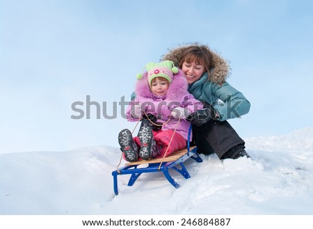 Mother and daughter sledging, nice winter scene - stock photo