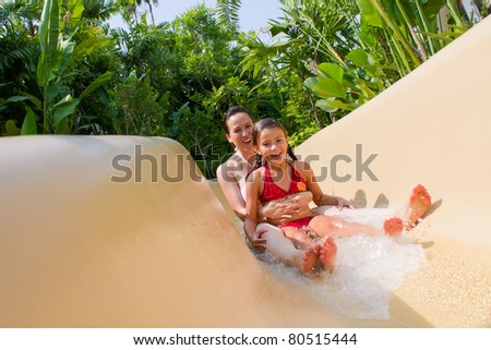 Mother and Daughter Sliding Down Water Slide. - stock photo