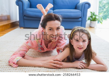 Mother and daughter smiling at camera at home in the living room - stock photo