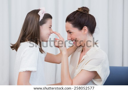 Mother and daughter smiling at each other at home in the living room - stock photo