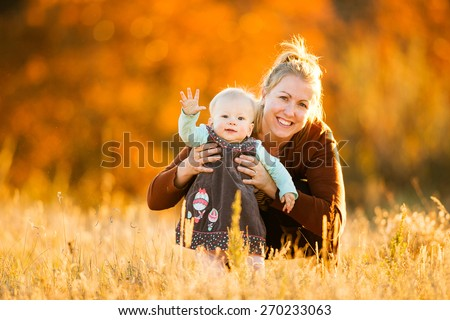 Mother and daughter smiling in a field - stock photo