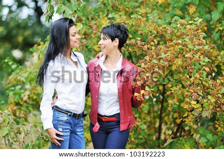 Mother and daughter smiling looking each other - stock photo