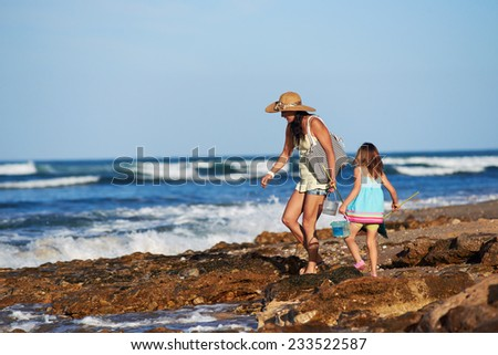 Mother and daughter spend the day fishing at the beach together having fun and bonding over some quality parent childhood time - stock photo