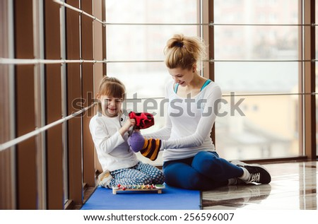 Mother and daughter spend time in the gym. - stock photo
