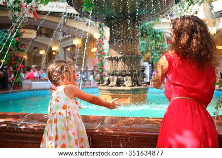Mother and daughter stand near fountain and play with jet of water - stock photo