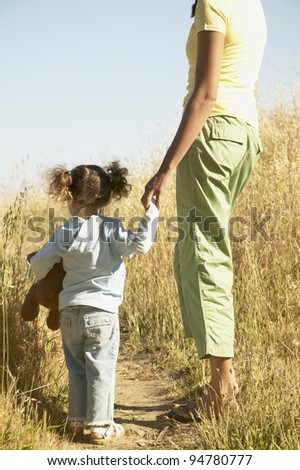 Mother and daughter standing in field - stock photo
