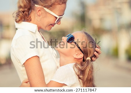 Mother and daughter standing on the road at the day time. - stock photo