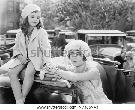 Mother and daughter standing together next to a car - stock photo
