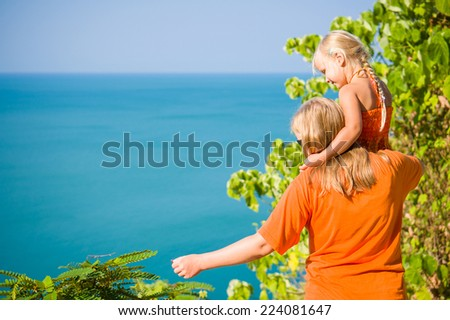 Mother and daughter stay on mountain road along tropical island beach and look at ocean - stock photo