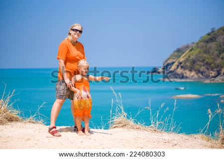 Mother and daughter stay on tropical island cliff and look at sea - stock photo