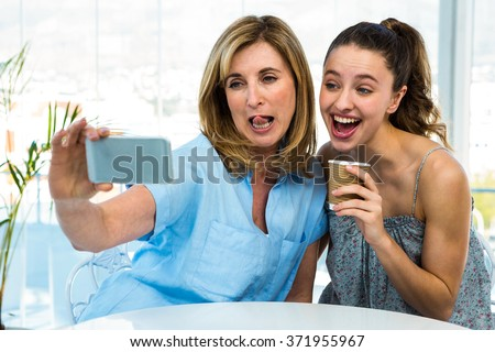mother and daughter take selfie with a phone and grimace - stock photo