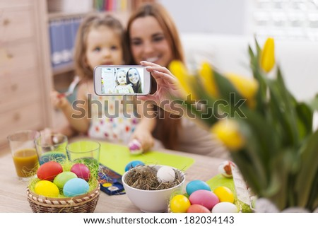 Mother and daughter taking self portrait while easter time - stock photo