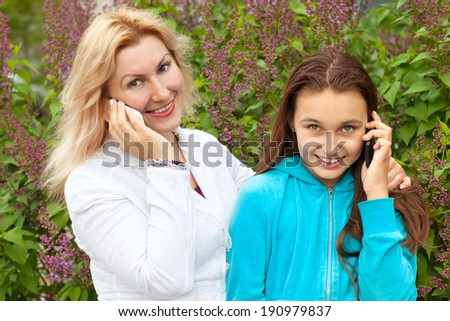 mother and daughter talk on phones - stock photo
