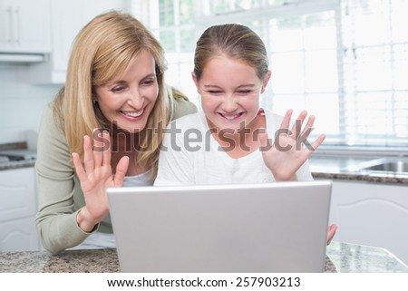 Mother and daughter talking with someone with the laptop at home in the kitchen - stock photo