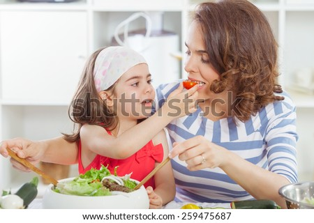 Mother and daughter tasting food they are preparing together in the kitchen - stock photo