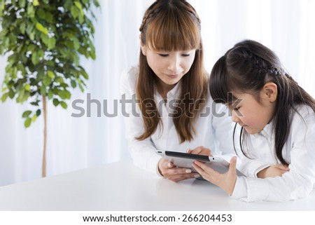mother and daughter to use a tablet PC - stock photo