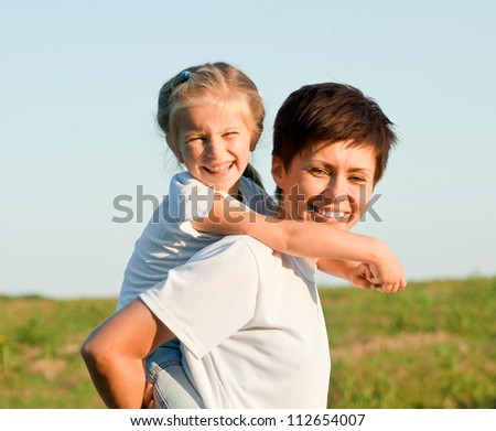 Mother and daughter together in a field - stock photo
