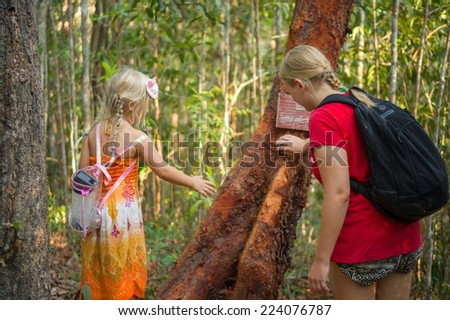 Mother and daughter touching tree with information poster at hiking trail to mountain top - stock photo