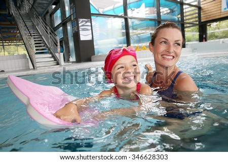 Mother and daughter training at the swimming-pool  - stock photo