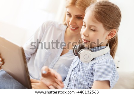 Mother and daughter using digital tablet - stock photo