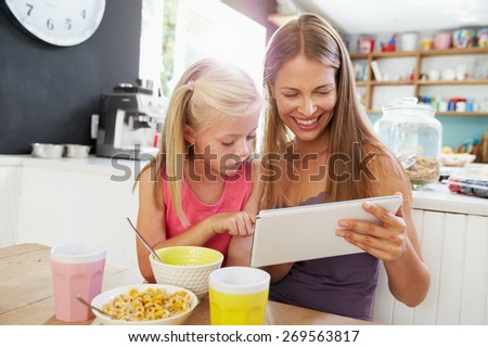 Mother And Daughter Using Digital Tablet At Breakfast Table - stock photo