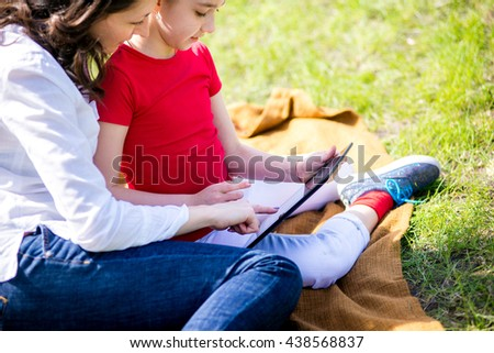 Mother and daughter using digital tablet while sitting in the beautiful nature,Mother and daughter using digital tablet - stock photo