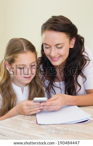 Mother and daughter using mobile phone together at table in house - stock photo