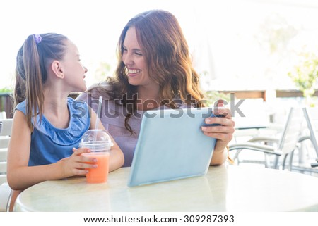 Mother and daughter using tablet at cafe terrace on a sunny day - stock photo