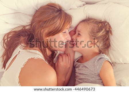 mother and daughter waking up with a smile - stock photo