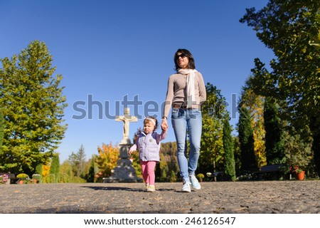 mother and daughter walking at church yard - stock photo