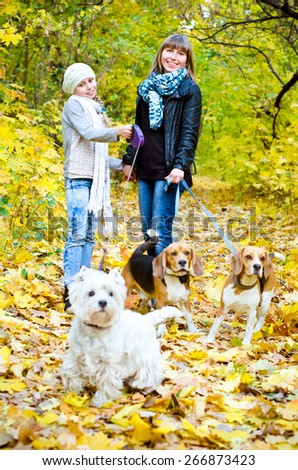 mother and daughter walking in the park with dogs - stock photo