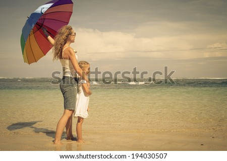 mother and  daughter walking on the beach at the day time - stock photo