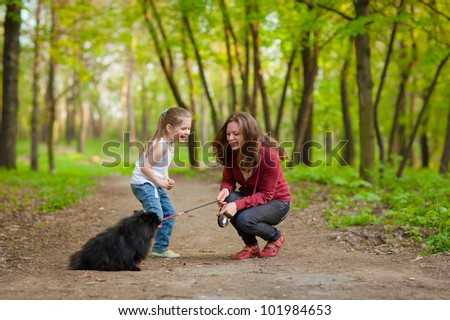 Mother and Daughter Walking the Dog - stock photo