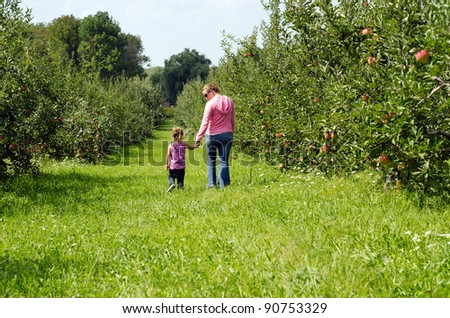 mother and daughter walking through a orchard - stock photo