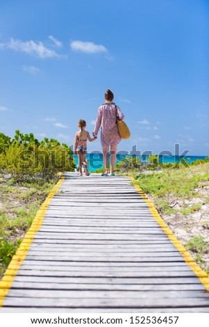 Mother and daughter walking to the beach along the wooden path - stock photo
